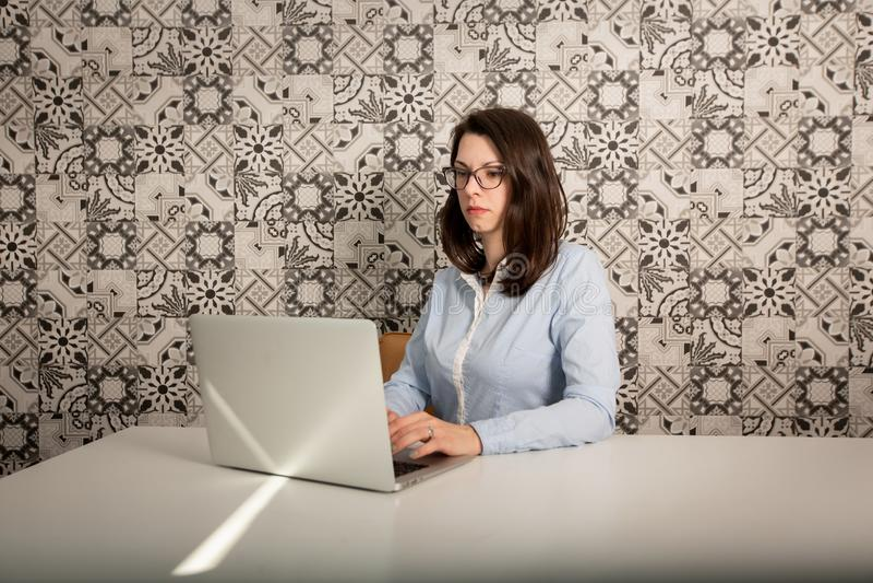 B?rande exponeringsglas f?r ung aff?rskvinna som sitter p? hennes skrivbord p? datoren, profilsikt i kontoret arkivfoto