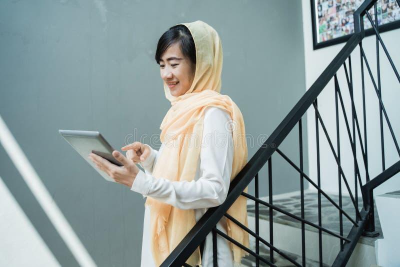 B?rande hijab f?r muslimsk kvinna genom att anv?nda minnestavlaPC royaltyfria bilder
