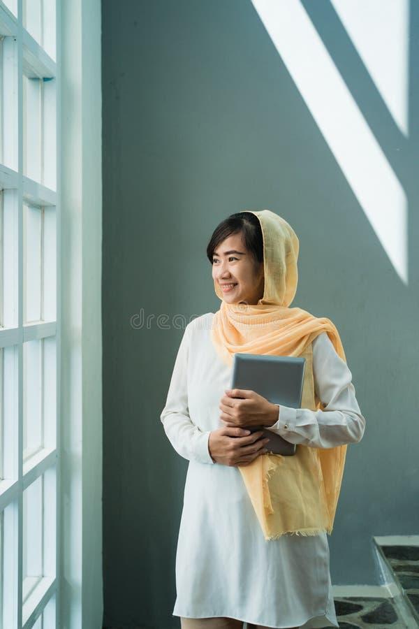 B?rande hijab f?r muslimsk kvinna genom att anv?nda minnestavlaPC royaltyfria foton