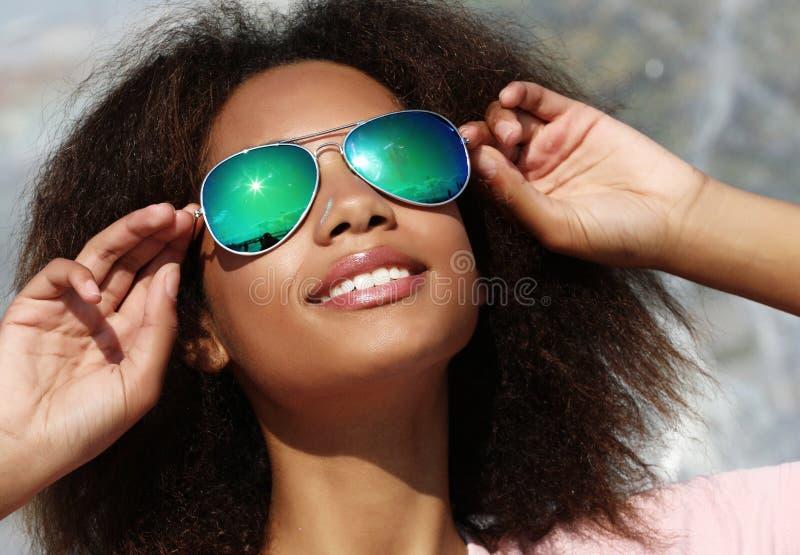 B?rande solglas?gon f?r n?tt kvinna med perfekta t?nder och m?rk ren hud som har att vila utomhus royaltyfri foto