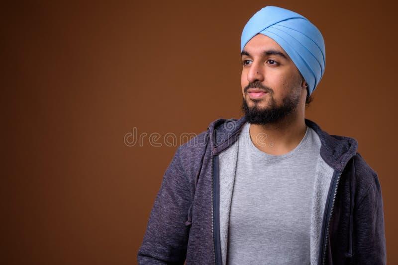 B?rande turban f?r ung sk?ggig indisk sikh- man mot brun backg royaltyfri fotografi