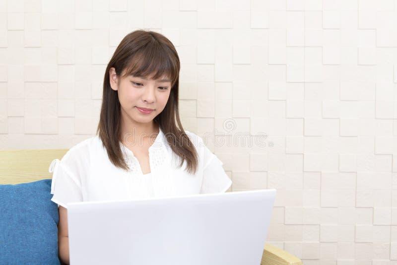 b?rbar dator som ler genom att anv?nda kvinnan royaltyfri foto