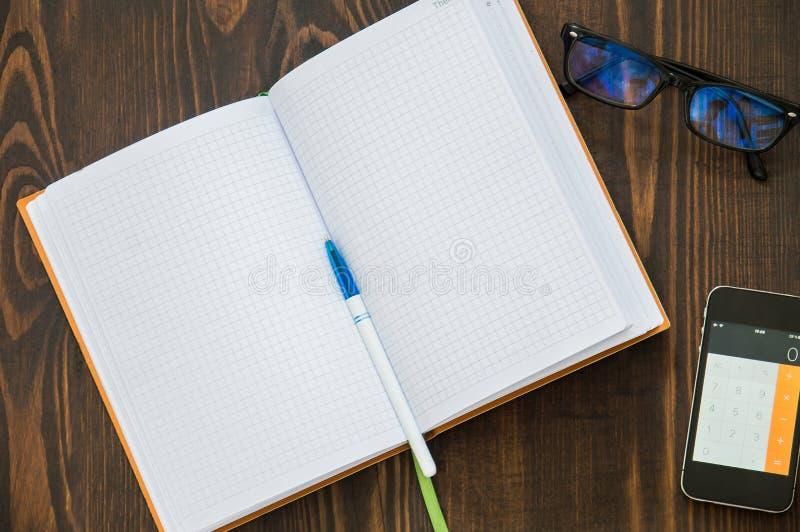 B?rbara datorn anteckningsboken, telefonen, penna l?gger p? golvet arkivbilder