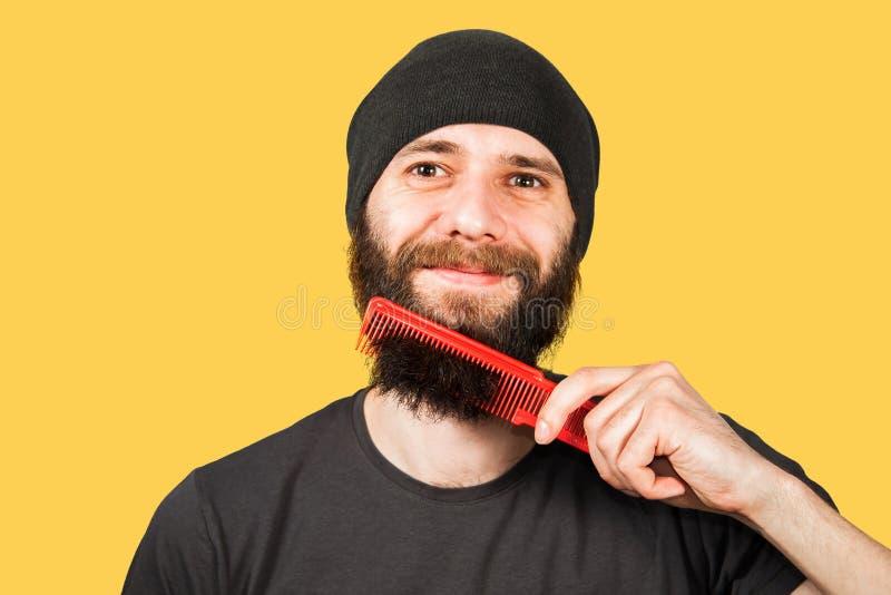 B?rtiger junger Kerl im Hut, der seinen Bart k?mmt Getrennt auf gelbem Hintergrund lizenzfreie stockfotografie