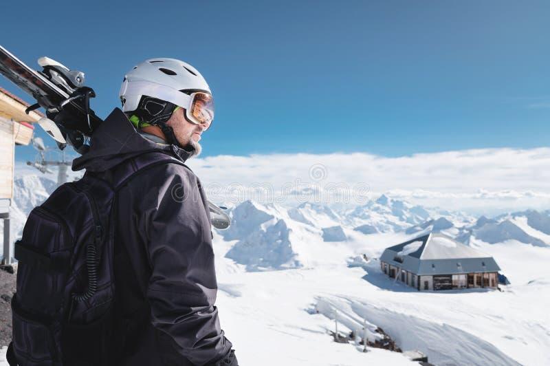 B?rtiger m?nnlicher Skifahrer des Nahaufnahme-Portr?ts gealtert gegen Hintergrund von Bergen Ein tragender Ski des erwachsenen Ma lizenzfreies stockbild
