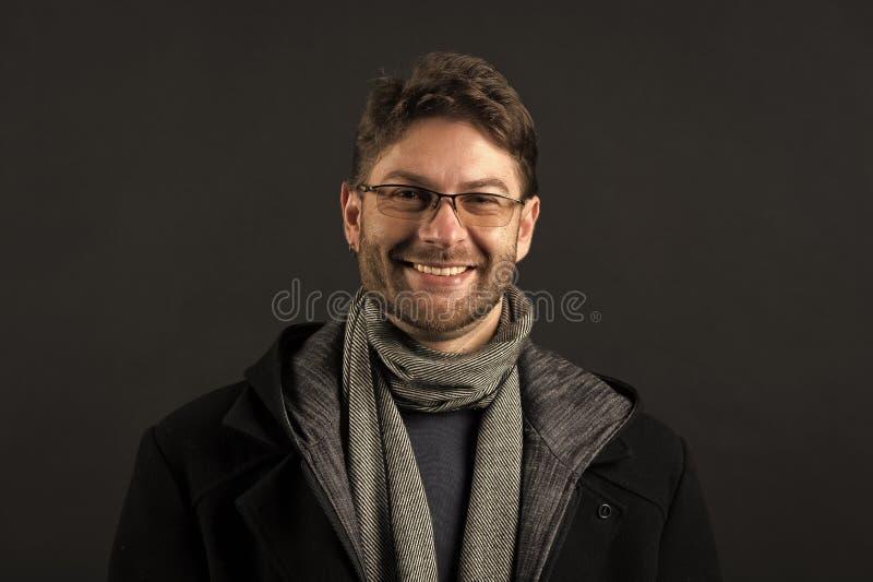 B?rtiger Mann im Schal und im Mantel auf dunklem Hintergrund Gl?cklicher Mann in den Gl?sern auf b?rtigem Gesicht Mode-Modell mit stockfotos