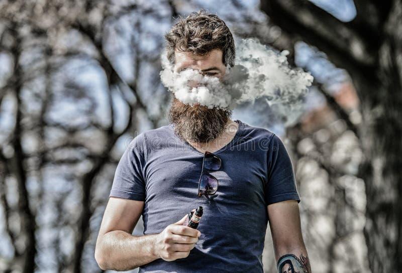 B?rtiger Mann rauchendes vape Rauchende elektronische Zigarette Langer Bart des Mannes entspannt mit Rauchen Mann mit Bart und lizenzfreie stockfotos