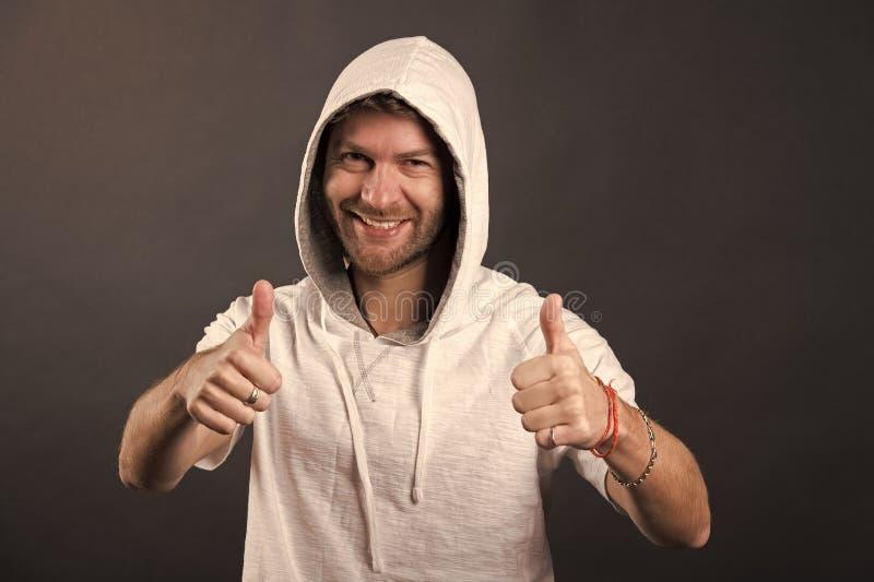 B?rtiges Mannl?cheln mit den Daumen oben Gl?cklicher Mann mit Bartabnutzungshaube Mode-Modell im Hoodiet-shirt Aktiver Lebensstil lizenzfreies stockfoto