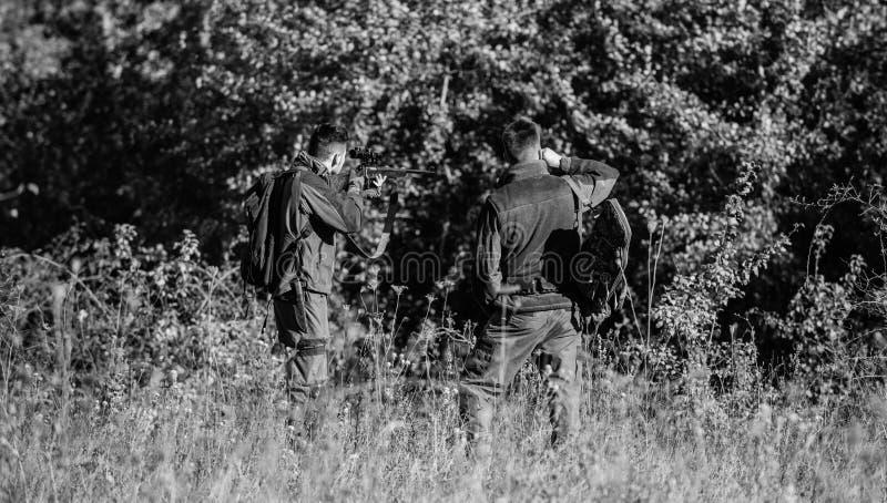 B?squeda con los amigos Los amigos de los cazadores disfrutan de ocio Trabajo en equipo y ayuda Concepto de los hombres de la act foto de archivo libre de regalías