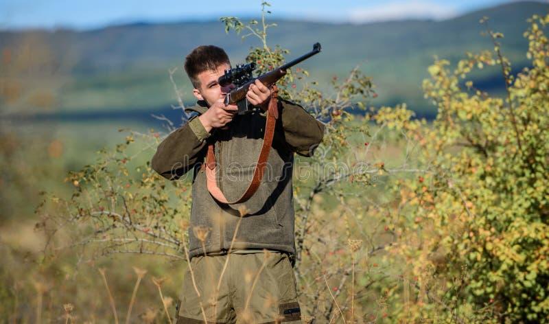 B?squeda del equipo para los profesionales La caza es afici?n masculina brutal Hombre que apunta el fondo de la naturaleza de la  foto de archivo
