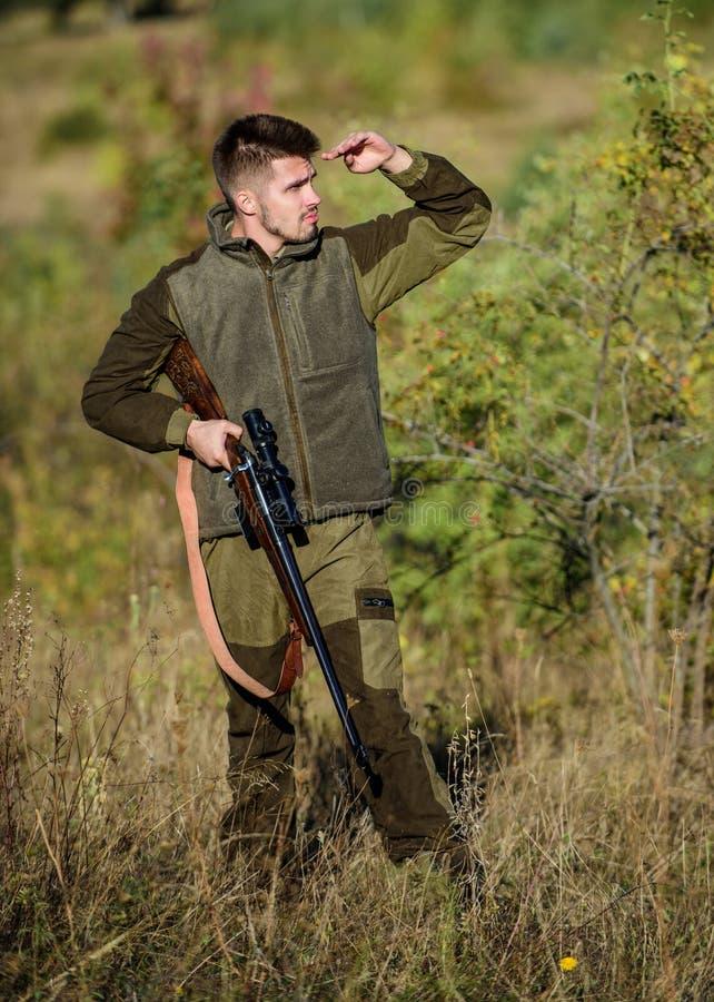B?squeda del permiso Cazador serio barbudo pasar la caza del ocio Rifle del control del cazador La caza es afici?n masculina brut imagen de archivo libre de regalías