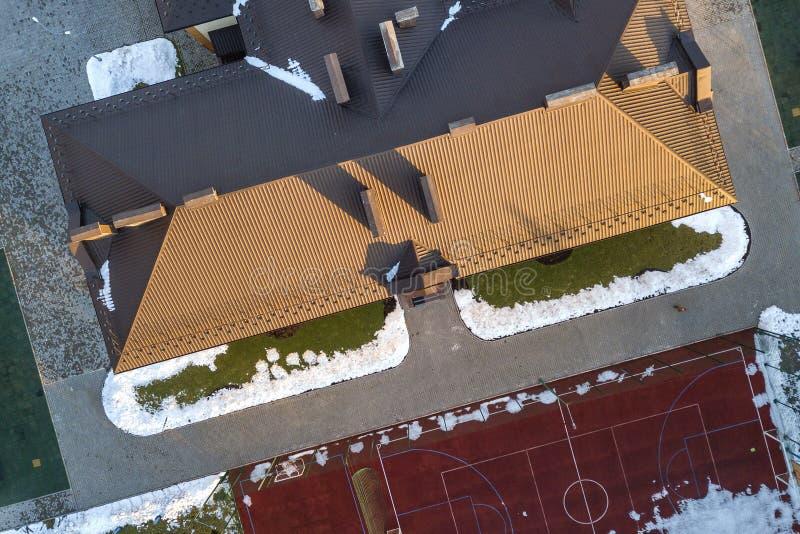 B?sta flyg- sikt av byggande av det belade med tegel taket f?r brun singel med komplex konfigurationkonstruktion Abstrakt bakgrun arkivfoto