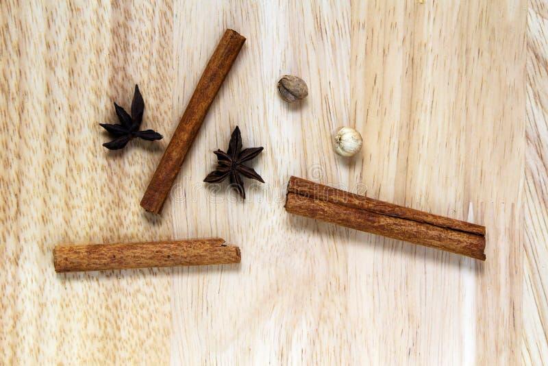 B?sta sikt av den kanelbruna pinnen med kryddor f?r stj?rnaanis och den torkade ingef?ran p? tr?skrivbordet royaltyfria foton