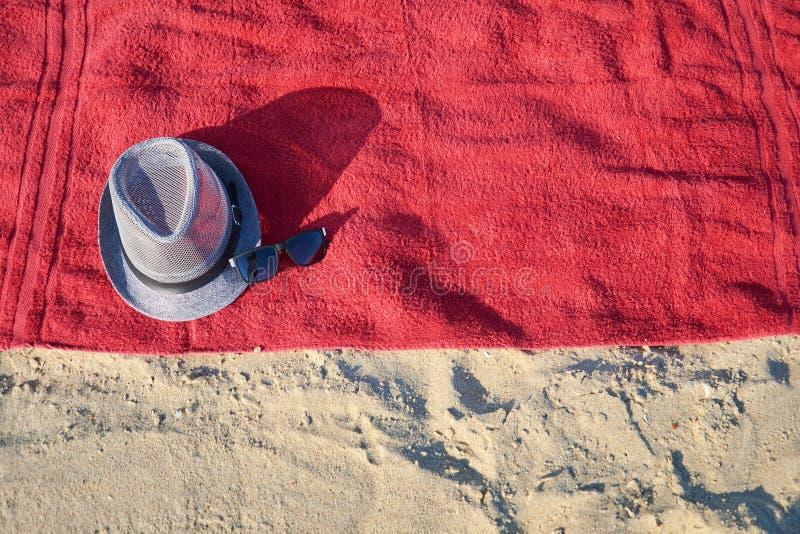 B?sta sikt av den sandiga stranden med handdukram- och sommartillbeh?r Bakgrund med kopieringsutrymme och synlig sandtextur arkivbild