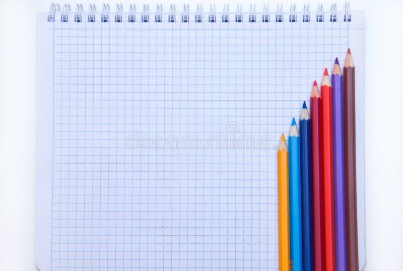 B?sta sikt av den tomma anteckningsboksidan med kul?ra blyertspennor p? tabellen Lekmanna- l?genhet arkivfoto