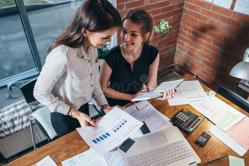 B?sta sikt av koncentrerade unga kvinnor som tillsammans sitter p? tabellen och arbetet arkivfoto