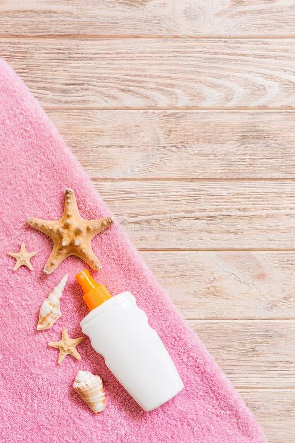 B?sta sikt av sommarstrandpersonalen med kopieringsutrymme Snäckskal eller seastar, en flaska av suncream och rosa handduk på trä arkivbilder