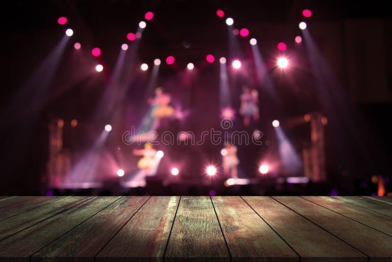 B?sta tr?skrivbord med ljus bokeh i konsertsuddighetsbakgrund, tr?tabell royaltyfri bild