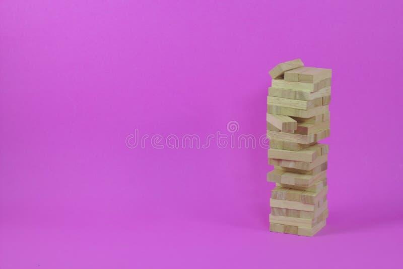 B?timent de jeu avec les b?tons en bois Dominos, bo?tes en bois, bo?tes en bois, pannes, fond rose images libres de droits