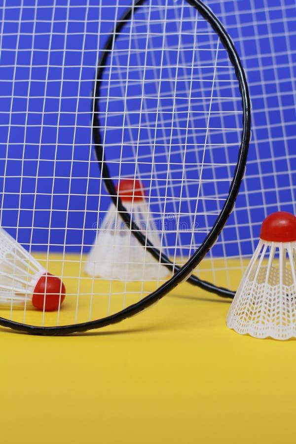 b?verskinn Tre fjäderbollar och racket för badminton två T arkivfoto