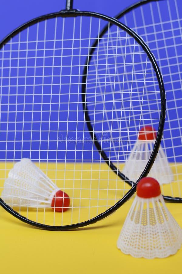 b?verskinn Tre fjäderbollar och racket för badminton två T arkivfoton