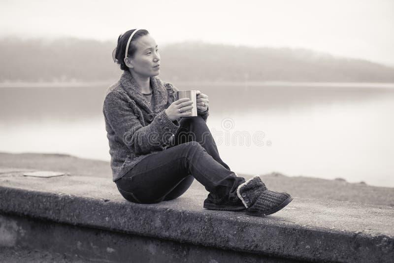 B&W de femme détendant par le lac image stock