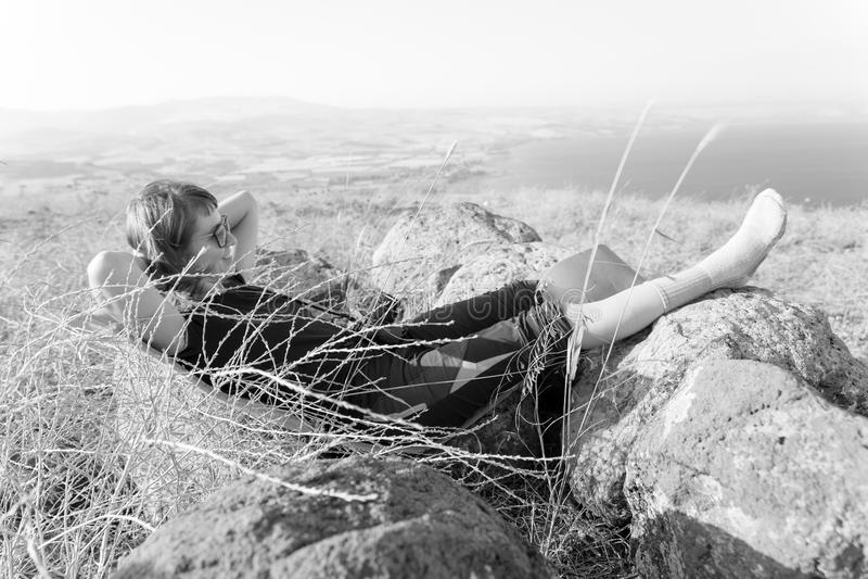 B&W jonge vrouw die terug in hoge het meermening van graskineret liggen stock foto