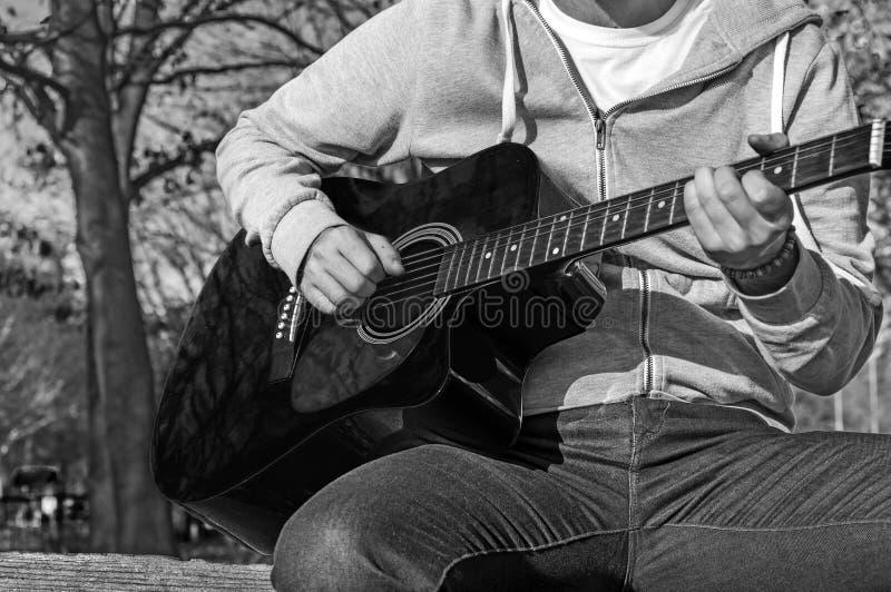 B&W - Młodego człowieka obsiadanie na drewnianym krześle w parkowej i bawić się gitarze fotografia royalty free