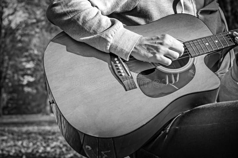 B&W - Młodego człowieka obsiadanie na drewnianym krześle w parkowej i bawić się gitarze zdjęcie stock