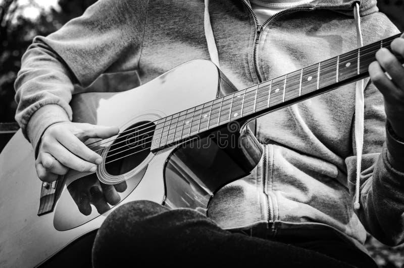 B&W - młody człowiek bawić się gitarę akustyczną na ławce w jesień parku obraz royalty free