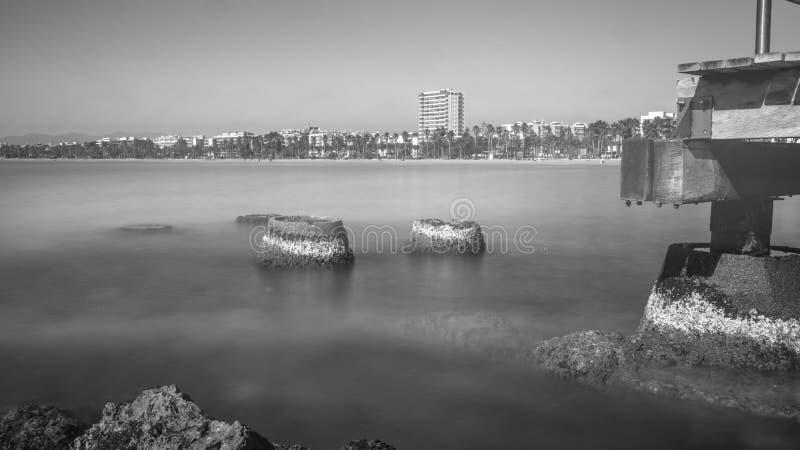 B/W Salou κύρια παραλία, δύο βάσεις ciment pilars όχι σε λειτουργία άλλα στοκ εικόνες