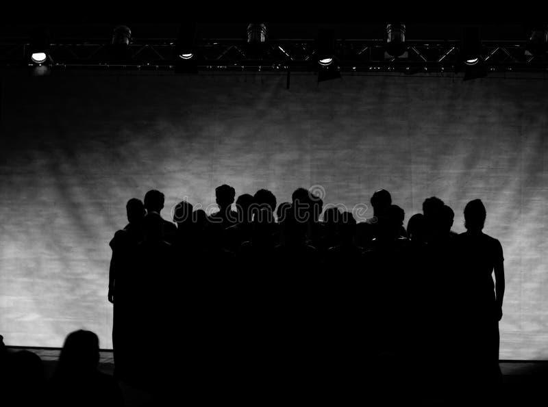 B&W: Schattenbilder von Leuten unter Stadiumslichtern stockfoto