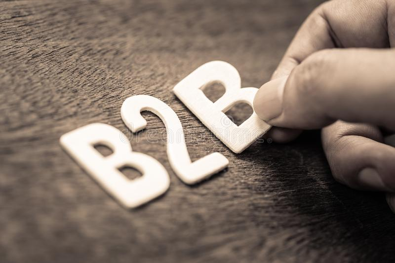 B2B Wood Letters. Hand place a wood letters as B2B abbreviation Business to Business stock images