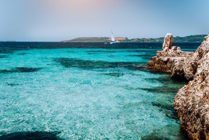 Baía acolhedor de turquesa bonita cercada pelos penhascos brancos Iate branco longe na água azul profunda Ilhas Ionian de imagem de stock