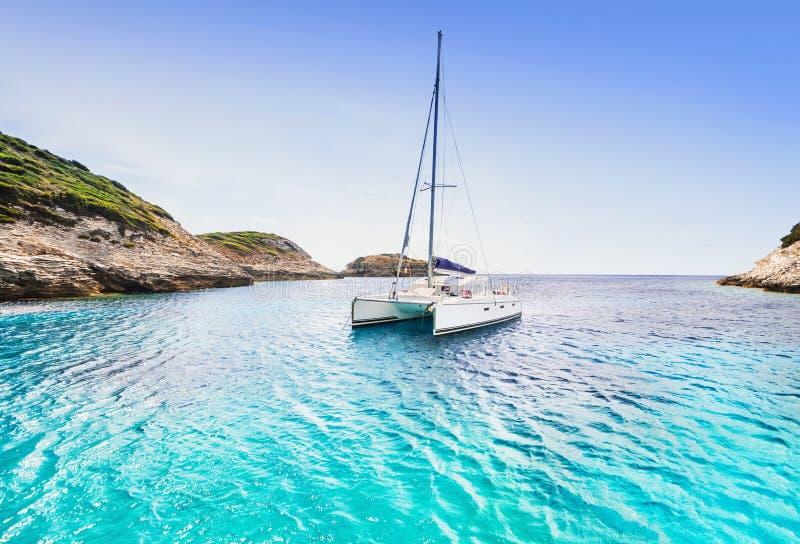 Baía bonita com o catamarã do barco de navigação, ilha de Córsega, França imagens de stock royalty free