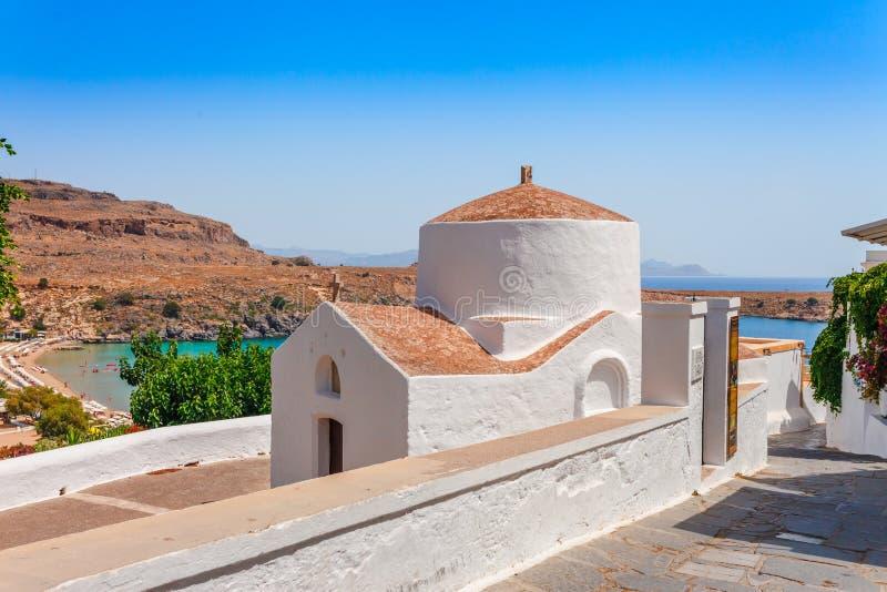 Baía e igreja ortodoxa da foto da paisagem do skyview do mar em Lindos na ilha do Rodes, Dodecanese, Grécia Panorama com a praia  foto de stock royalty free