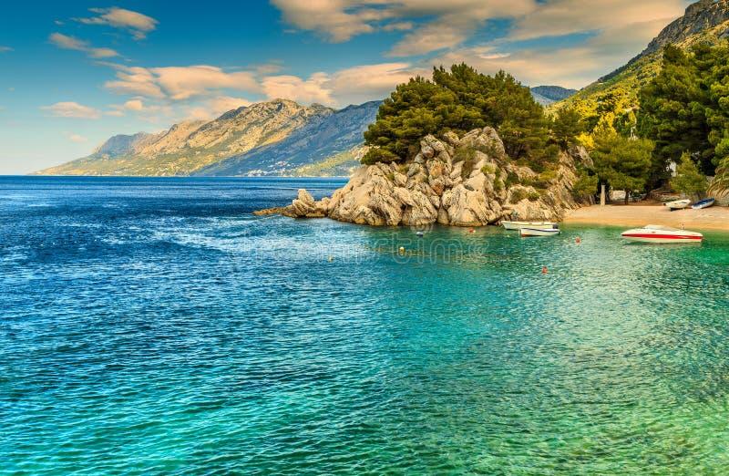 Baía e praia bonitas com barcos a motor, Brela, região de Dalmácia, Croácia, Europa foto de stock