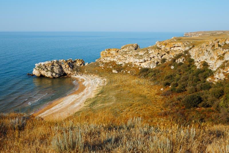 Baía e Sandy Beach selvagens do mar nas rochas no por do sol foto de stock royalty free
