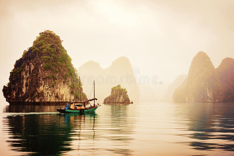 Baía longa Vietname do Ha do barco de pesca no por do sol fotografia de stock