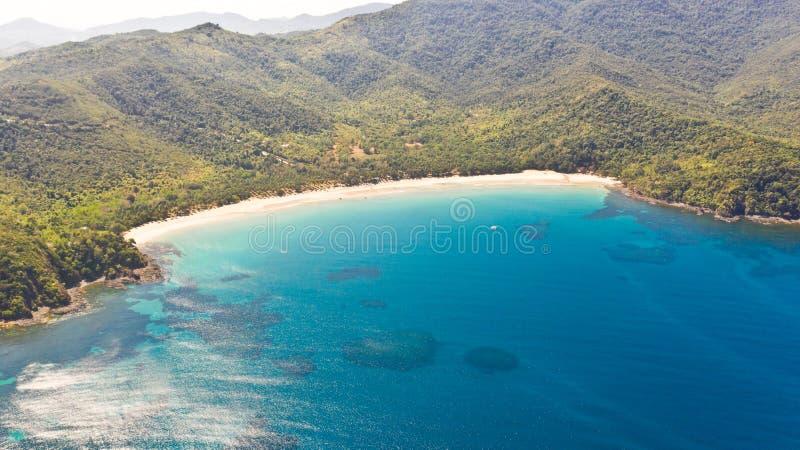 Baía marítima com água turquesa e uma pequena praia branca Linda lagoa e ilha vulcânica coberta de densa floresta, vista de imagem de stock