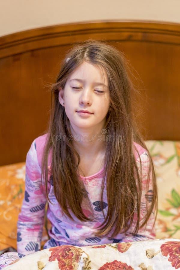 Baîllement somnolent d'enfant dans le lit Somnolent petite fille sur le lit Photo verticale photo libre de droits