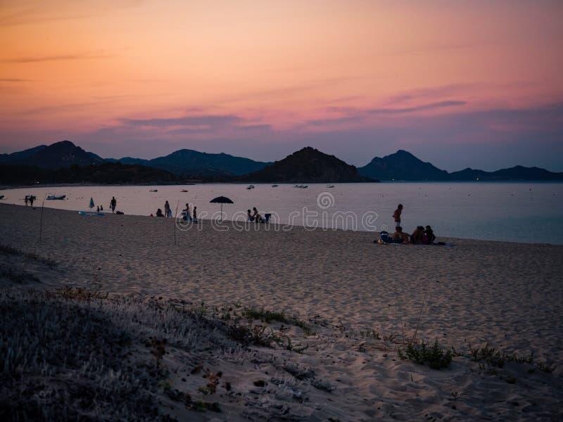 Bañistas en la puesta del sol en una playa arenosa de Cerdeña del sur fotografía de archivo libre de regalías