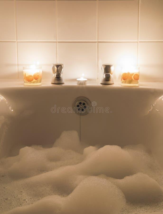 Baño de burbujas y velas imagenes de archivo