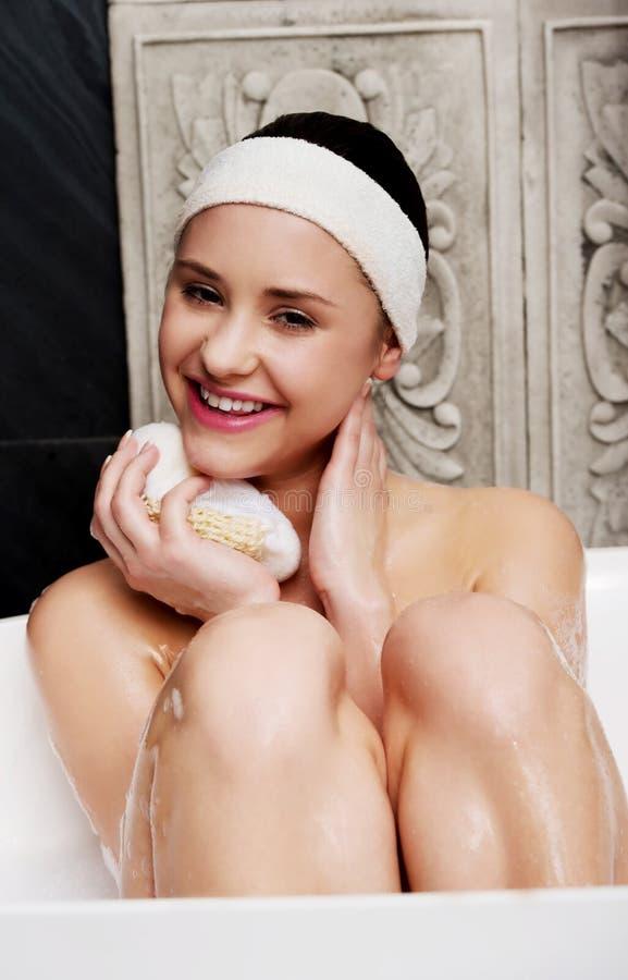 Baño de la mujer que se relaja con la esponja imagen de archivo
