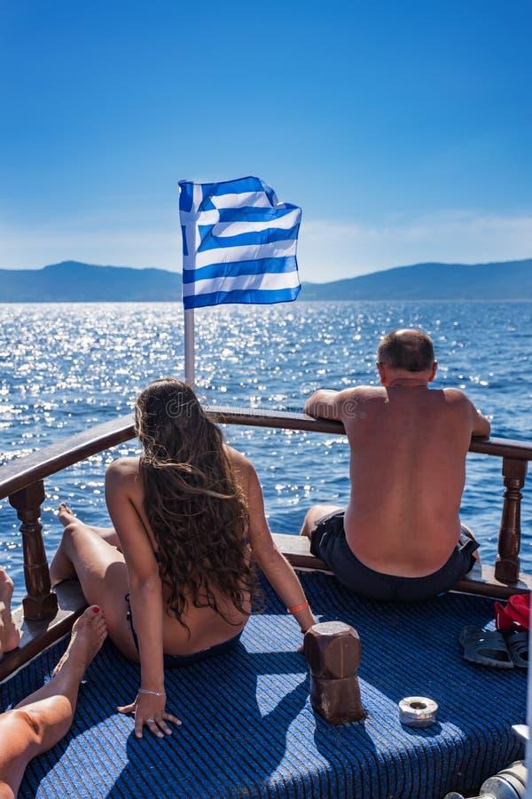 Baño de sol de la chica joven y del hombre delante de la bandera griega en el barco de fotografía de archivo libre de regalías