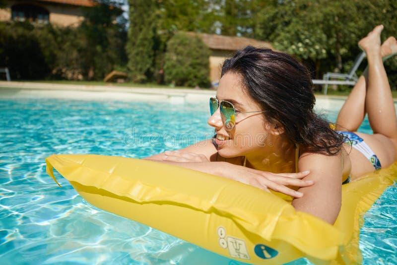 Baño de sol de la mujer joven en piscina del balneario imágenes de archivo libres de regalías