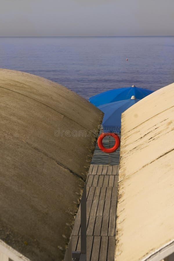 Baño del parasol de playa de la choza y del chaleco salvavidas imagen de archivo