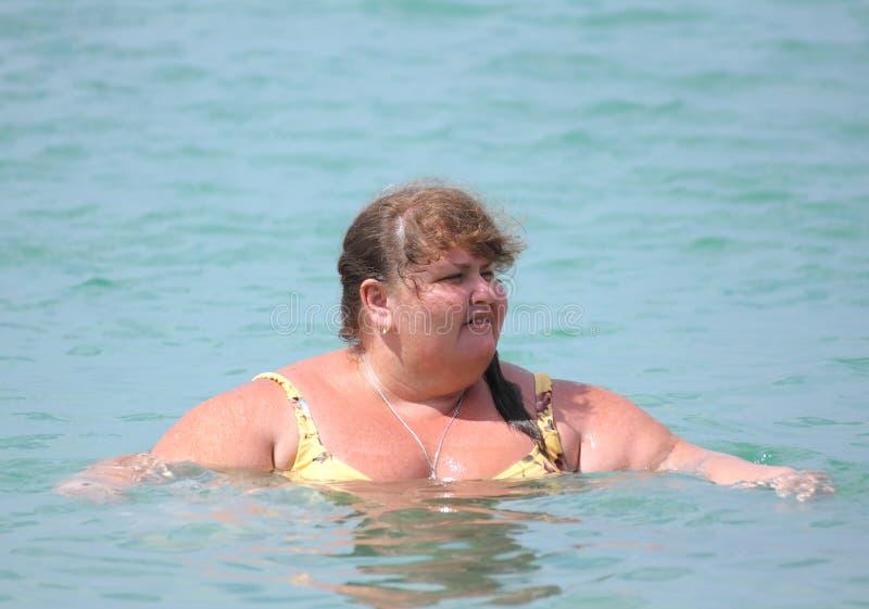 Baño regordete de la mujer en el mar fotografía de archivo libre de regalías