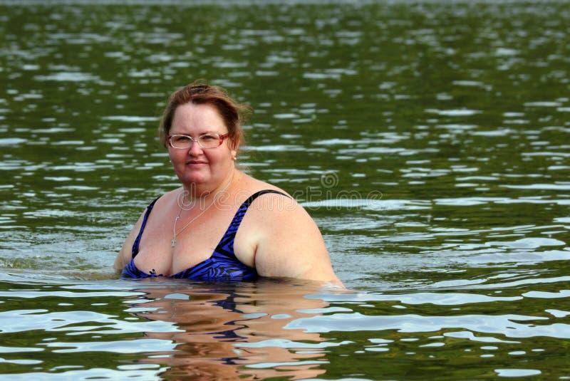 Baño regordete de la mujer en el río fotos de archivo