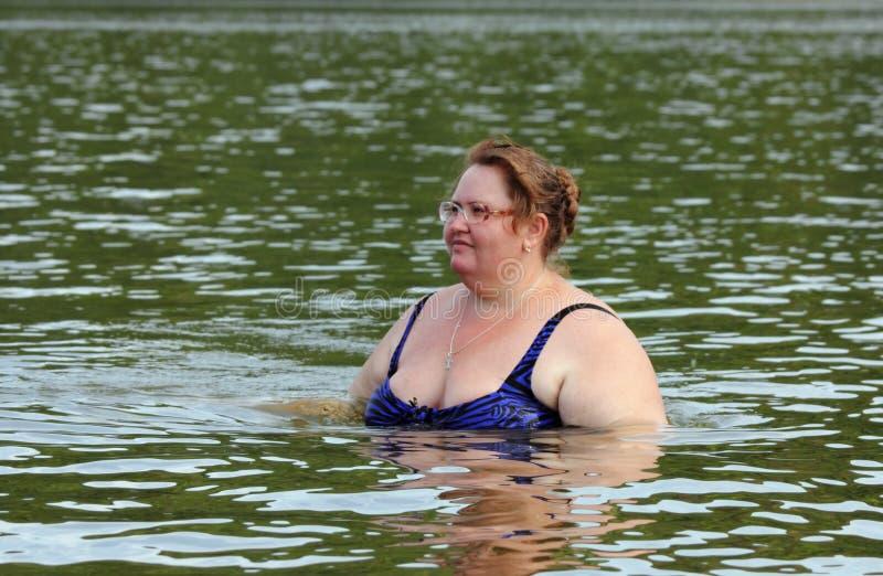Baño regordete de la mujer en el río imagen de archivo